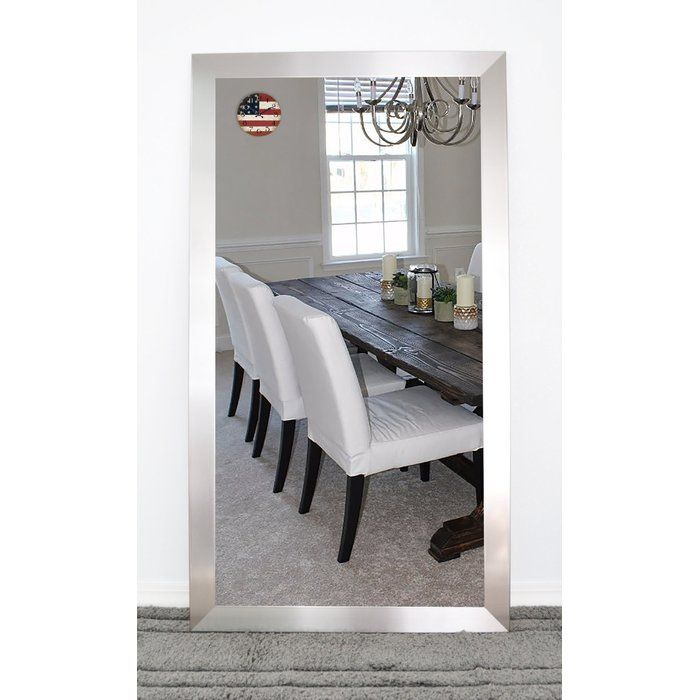 Made in the USA, this minimalist mirror features a flat panel of glass in a sleek brushed nickel frame, and can be wall-mounted or leaned. For a contemporary ensemble in your bedroom, start by rolling out a white shag area rug to define the space, then arrange a lacquered wood nightstand with chrome legs on each side of a low-profile platform bed. Lean this streamlined mirror against the wall outside your closet, then add bold accents to brighten up the space, including a potted fiddle leaf…