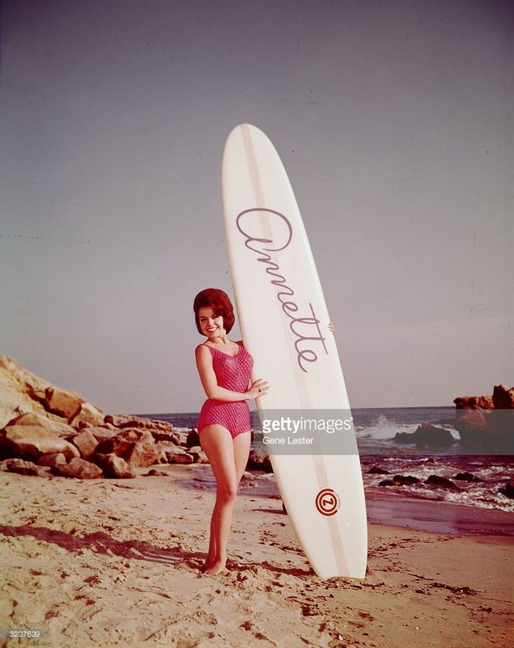 Full-length promotional photo of American actor and singer Annette Funicello posing on the beach with a surfboard bearing her name, for her album, 'Muscle Beach Party'. She wears a swimsuit.