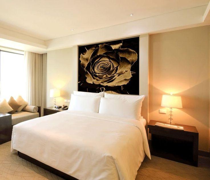 Fototapeta z różą w sepii nad łóżkiem w sypialni