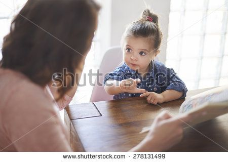Cute girl with mom reading a book  - stock photo
