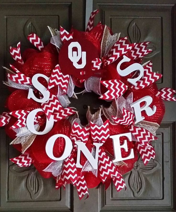 """This is a beautiful 24"""" deco mesh Oklahoma Sooners wreath. The wreath is made of red deco mesh and accented with cream and white ribbon and red and white chevron ribbon. It also has a hand painted OU"""
