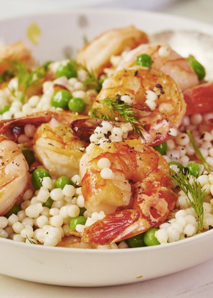 Roasted Shrimp and Pea Couscous Salad. If you're looking for ideas for quick and easy weeknight dinners and meals, you'll live this simple and easy pasta recipe! Recipes like this are both healthy and delicious - perfect for spring time. You'll need lemon juice, shallot, frozen or fresh peas, dill, dijon mustard,  Israeli (pearl) couscous, water, shrimp.