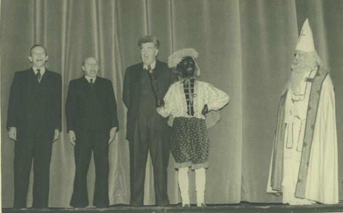 Sinterklaas, in witte mantel, een Zwarte Piet en een aantal onderwijzers op het toneel tijdens één van de uitvoeringen van een sprookje opgevoerd voor de leerlingen van de Rooms-katholieke lagere en ULO scholen en hun ouders rond de Sinterklaasperiode in schouwburg De Harmonie in Leeuwarden. Foto gemaakt circa 1956-1959.