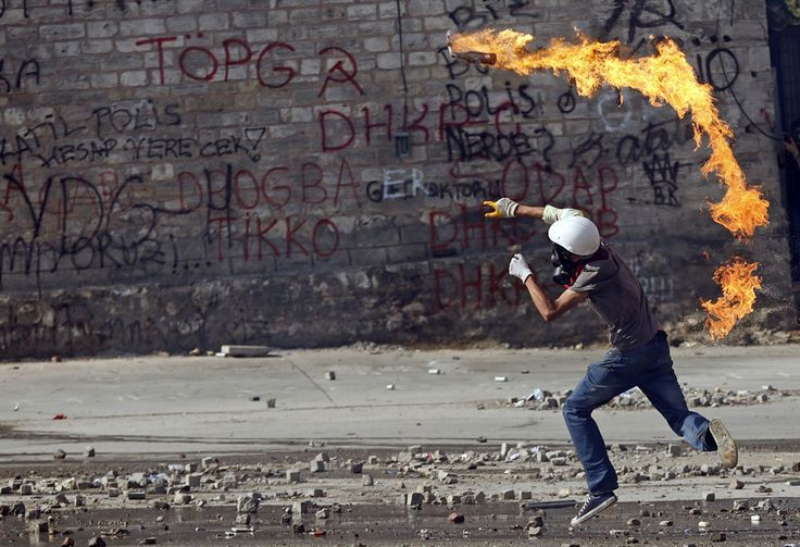 A protester throws a petrol bomb at riot police in Taksim Square, on June 11, 2013