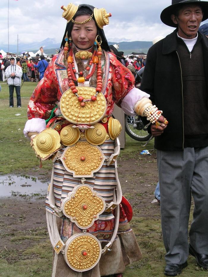 Litang Horse festival.Mujer vestida con la joyería y los amuletos tradicionales,lleva decenas o cientos de miles de dólares de los ahorros familiares,que pueden pesar 20 kgs o más,los suelen vestir dos veces al año en festivales de verano o bodas.