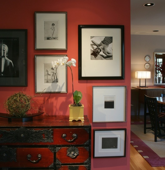 Colorful rancher, asian inspired, Antique tansu holds accessory treasures. A bold coral accent wall sets off black and white artwork.