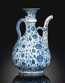 A LARGE 'ABRAHAM OF KUTAHYA' BLUE AND WHITE IZNIK POTTERY EWER   OTTOMAN TURKEY, CIRCA 1510   Rising from wide round foot to bulbous body tapering to thin neck with pronounced collar terminating in wide flaring mouth, curved serpentine handle and vertical spout with curved finial, painted in cobalt-blue on white ground with scrolling palmettes, the base of the spout outlined with cusped medallion, the foot decorated with overlaping chevrons, the bridge between the spout and neck with…