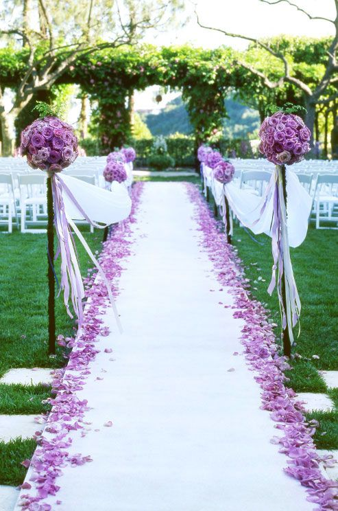 The end of the aisle was marked by two tall floral balls of purple roses.
