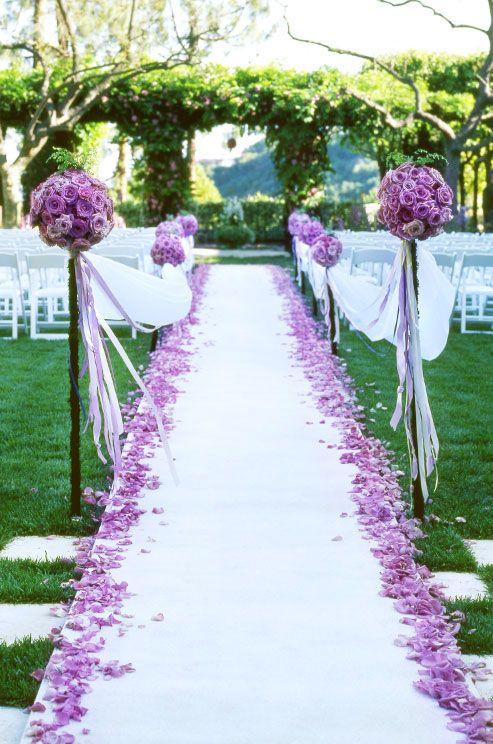 Decoración en tonos morados para el lugar de la ceremonia. The end of the aisle was marked by two tall floral balls of purple roses.