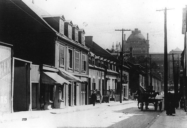 """Montréal 1915. Rue Cadieux >Sud, depuis rue de La gauchetière.  Archives du Musée McCord.    Ayant déjà porté le nom de rue Saint-Constant ,actuellement rue de Bullion. En 1915, cette rue se rendait, au Sud, jusqu'à la rue Craig (rue Saint-Antoine) qu'on entrevoit au loin à droite .Elle était bordée d'anciennes maisons à logements jumellées à des commerces au rez-de-chaussée. Ce secteur a déjà porté le nom de """"quartier juif """".Comparatif du 23 juin 2011…"""