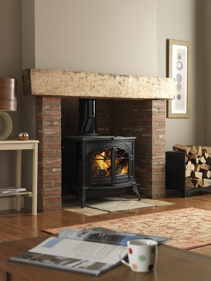 Sometimes you can't beat the classics. Earthy tones, red brick, wood mantel and a traditional stove.
