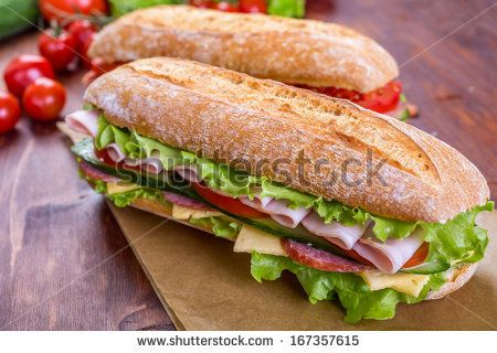 Two Long Ciabatta Sandwiches with lettuce, slices of fresh tomatoes, cucumber, ham, salami and cheese - stock photo