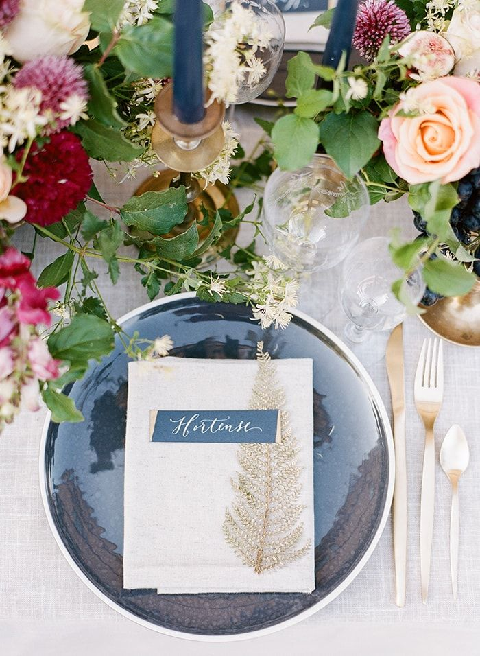 Gorgeous table setting with blue and gold details. Garden roses and greenery.
