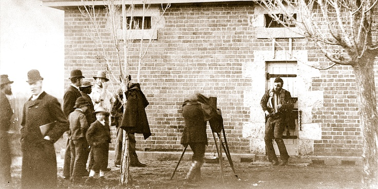 On 29 June 1880, a day after the destruction of the Kelly Gang, the Victoria Police decided to display the body of Joe Byrne on the door of the Benalla lock-up. Photographer J.W. Lindt recorded his colleague Arthur Burman photographing the body. At the far left, press artist Julian Ashton has turned his back on the macabre spectacle. The previous night Ashton sketched Joe's corpse onto a wooden tablet. The drawing was then engraved for reproduction in the 'Illustrated Australian News'.