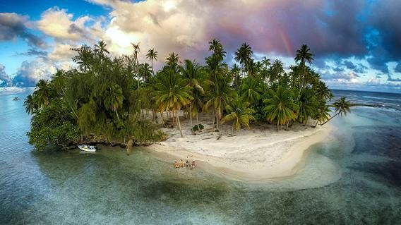 A rainbow appeared just in time for these swimmers as they waited for a sunset in French Polynesia. (Source: Dronestagram,  Marama Photo Video)