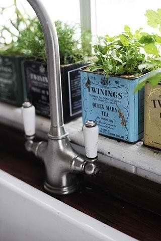Window herb garden with vintage tea cans