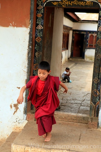 Off to Lunch - Chimi Lhakhang Monastery in Bhutan. I also like the depth of field background blur, where the seated boy looks back out of the doorway towards our main subject.