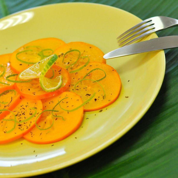 Prélevez le zeste des citrons verts avec un zesteur. Ciselez la menthe.Lavez le kaki et séchez-le.Coupez-le en tranches très fines.Disposez les tranches dans une assiette, parsemez de zestes de citron et de menthe. Ajoutez un filet de jus de citron.Servez bien frais.