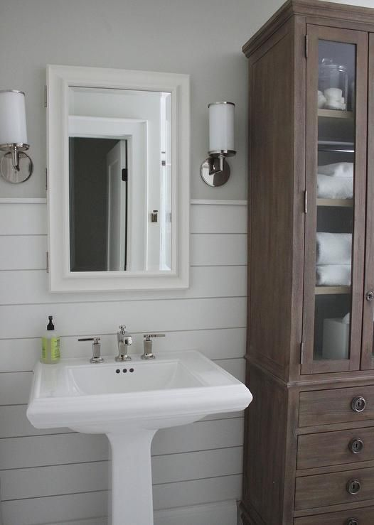 Beautiful bathroom features upper walls painted gray and lower walls clad in shiplap lined with a pedestal sink under a white framed medicine cabinet illuminated by white glass sconces next to a stained linen cabinet with glass doors.