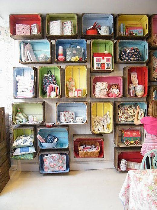 I want this wall... somewhere... Painted crates are attached to a blank wall, providing a home to toys and objects of various sizes in this sweet playroom.  Source: Nietylko Dzieciak