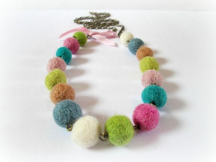 Este alegre collar está hecho con bolitas de fieltro de 10 mm engarzadas formando una cadena multicolor de pompones. Los pompones cuelgan de una cadena de aleación de cobre en tono bronce...