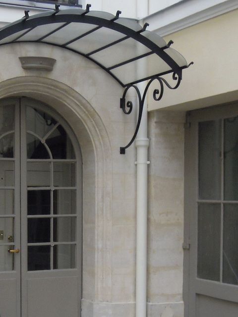 .arched wrought iron door awning What do you think the top is...can't be plastic. Maybe we could use canvas. Hmmm.
