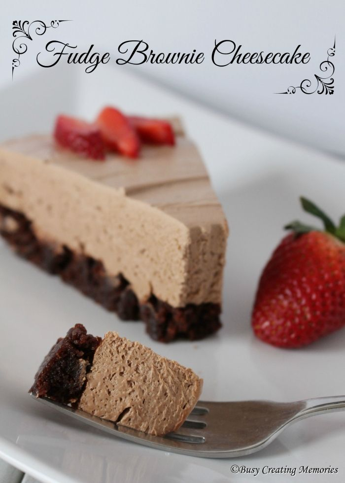 Delicious Fudge Brownie Cheesecake topped with sweet and fresh strawberries.