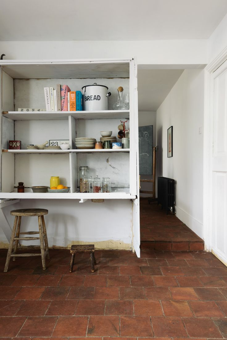 Beautiful Terracotta floor tiles and old original storage added to the charm of this rustic Shaker kitchen