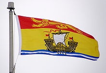 The flag of New Brunswick, Canada_is a banner modelled after the province's coat of arms & was adopted by proclamation on February 24, 1965.  The flag has proportions 8:5. A gold lion on the red field across the top 1/3 of the flag represents New Brunswick's ties to both the Brunswick region in Germany & (the arms of) the Monarch of Canada. The lower 2/3 of the flag depicts a Scottish Lymphad, the traditional representation of a ship in heraldry. It represents shipbuilding, one of the…