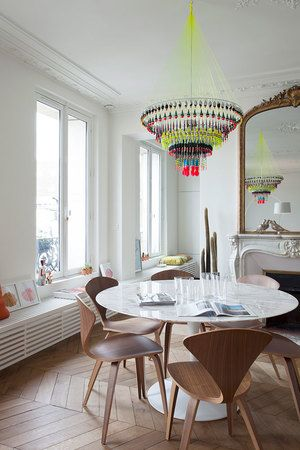 Parisian dining room with mid century furniture & neon-colored chandelier