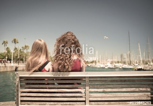 Girls on the bench watching the harbor