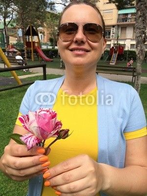 Happy woman holding a rose in her hand