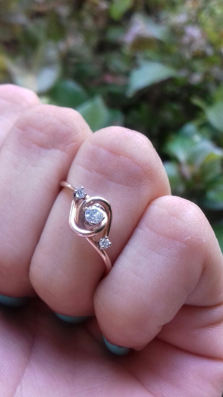 Hermoso anillo de compromiso con un total de 3 simbólicos diamantes naturales, el diamante central es de Ctw 0.08 puntos, Corte Redondo, Color F-G, Claridad SI2 de 14 kilates color Rosa el peso total de esta delicada pieza es de 1.4 gramos a los extremos de el diamante central tiene dos diamantes de corte redondo con un total de 0.04 puntos de diamante. Este anillo esta diseñado a mano haciendo semejanza a una enredadera  *Disponible en todas las tallas  Garantía de por vida  Certificado…