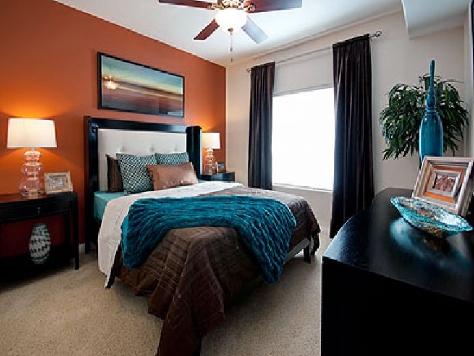 the orange accent wall with teal and brown bedding is - Brown And Orange Bedroom Ideas