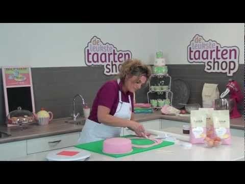 Een taart bekleden met een laag marsepein, het lijkt een hele klus maar wij leren je in deze video hoe het moet. We laten zien hoe je de marsepein uitrolt en over je taart heen legt en hoe je vervolgens een mooie strakke laag marsepein op je taart krijgt. Dezelfde technieken kun je ook gebruiken om een taart te maken bekleed met fondant.
