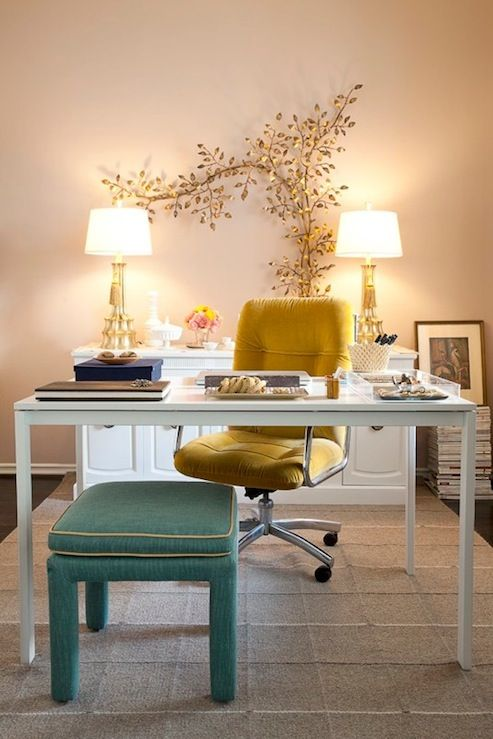 Domicile ID    Chic eclectic office design with gold art wall sculpture, white desk, yellow velvet office chair, Hollywood Regency green ottoman with yellow piping, gray rug and white credenza.