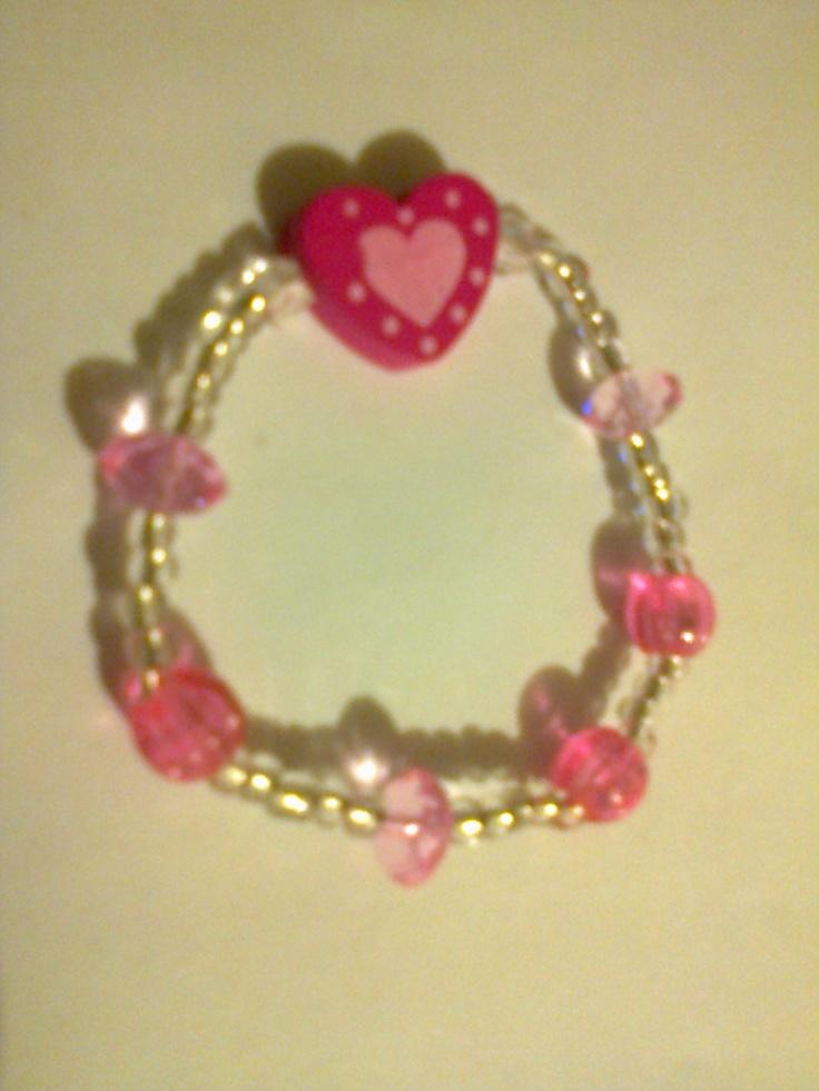 KA_P015 - Pulsera en colores transparente y rosa con cuenta de madera en forma de corazón.