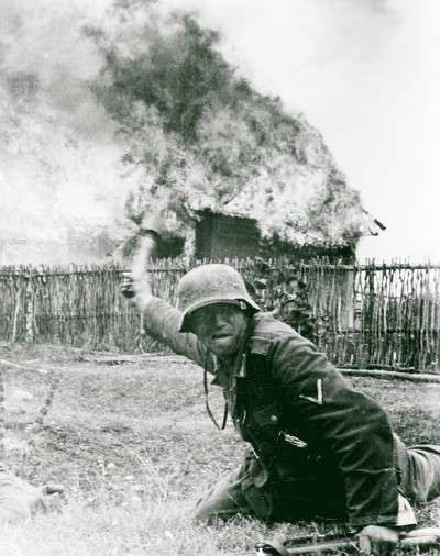 German soldier throwing stick grenade, while a  house is burning behind him. operation Barbarossa 1941