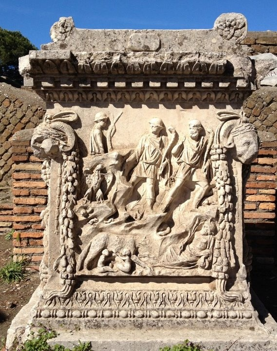 Altar at Ostia Antica. This altar shows Romulus and Remus fed by the She-wolf of Rome (lower left corner), surrounded by representations of the Tiber and the Palatine. The alter was dedicated to the divine couple of Mars and Venus. This is a reproduction of the altar discovered on the site, the original is in the Palazzo Massimo in Rome.