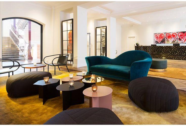 Hotellets lobby med gott om sittmöjligheter. Sittgrupp med svarta puffar, blå soffa och tre soffbord med ljuslyktor på.