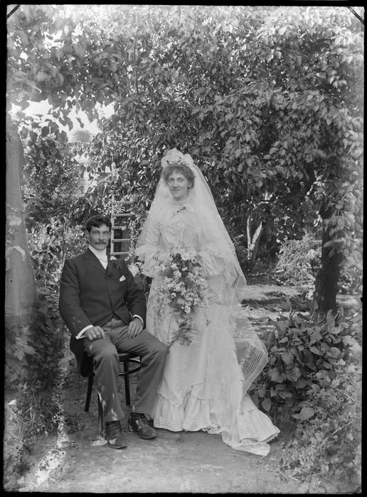 Outdoors unidentified wedding couple portrait under trees, groom with moustache sitting next to bride with long veil holding flowers standing, probably Christchurch region