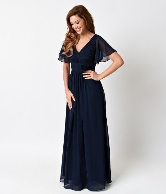 Dreamy and gorgeous! This beautiful pleated empire waist gown is accented with a ruched flower on the waistline. This navy blue long dress is complete with alluring v-neck and flowing short sleeves.