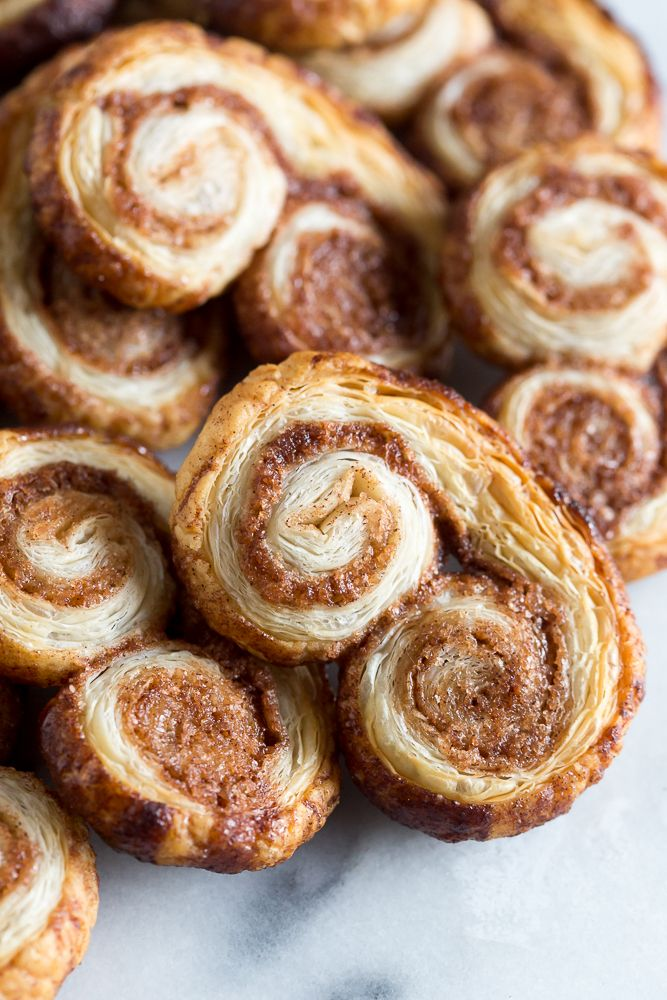 These cinnamon sugar palmiers are ready in under 20 minutes and are sure to please everyone. Perfectly sweet crunchy and made with store bought puff pastry. You'll love these cookies!