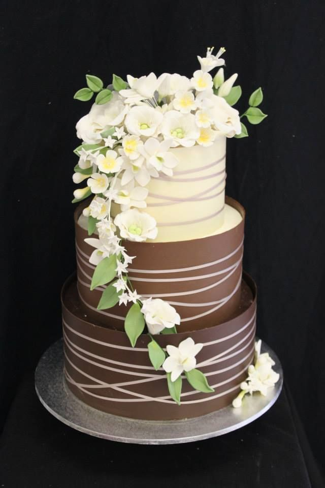 A gorgeous criss-cross chocolate collared cake with cascading flowers
