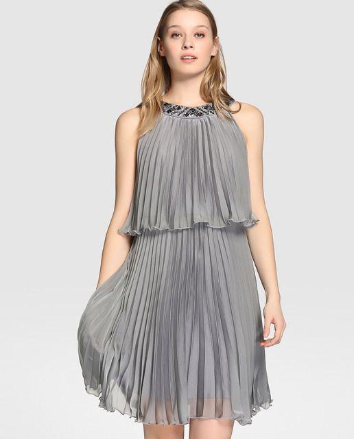 Vestido corto, en color gris, con plisados. Tiene escote halter con pedrería, efecto dos piezas y cierre en la espalda.