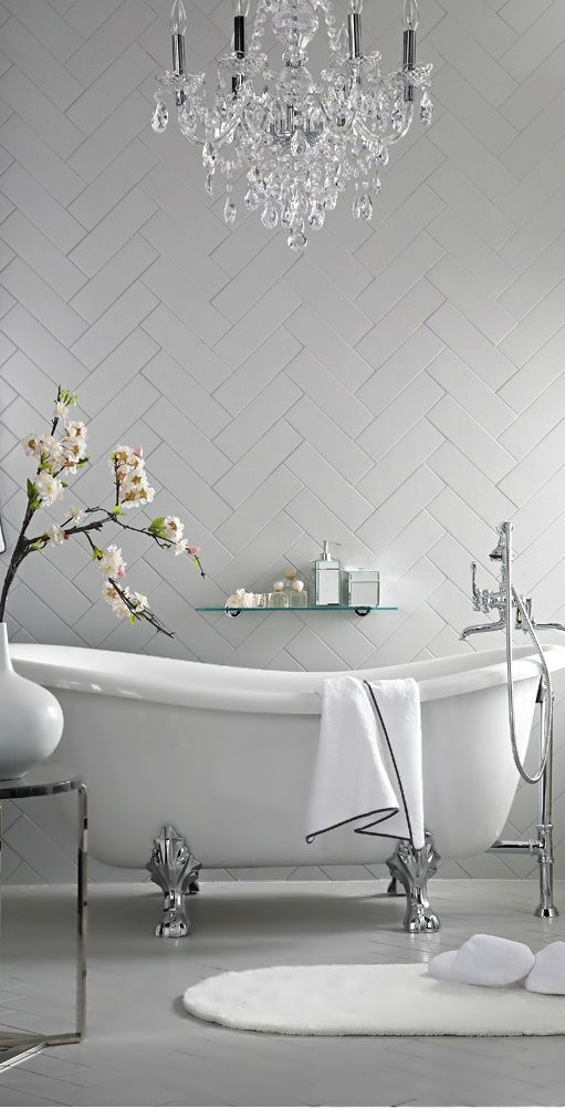 The lines in this bathroom, from the chevron ceiling and flooring to the curves of the bathtub are so beautiful