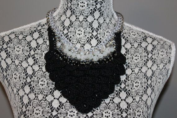 Hand made crochet crocodile stitch bib necklace in black thread with silver accents and white, silver & black beads. Attached to a blackened
