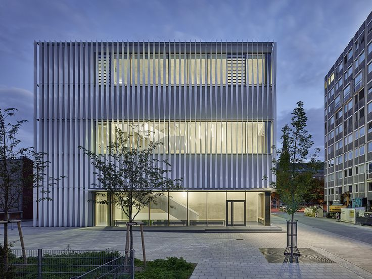 Gallery of Sporthalle Kepler- und Humboldt-Gymnasium in Germany by h4a Architekten: the 18 m high cubic building is covered by a structure of brilliant white shiny aluminum fins in vertical order and slightly rotated