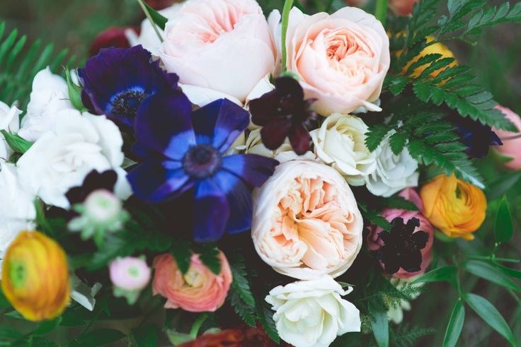 Whimsical Forest Wedding Inspiration via Rocky Mountain Bride (Look at that deep, deep blue anemone highlighted by the pale orange-pink garden roses, and golden ranunculus)