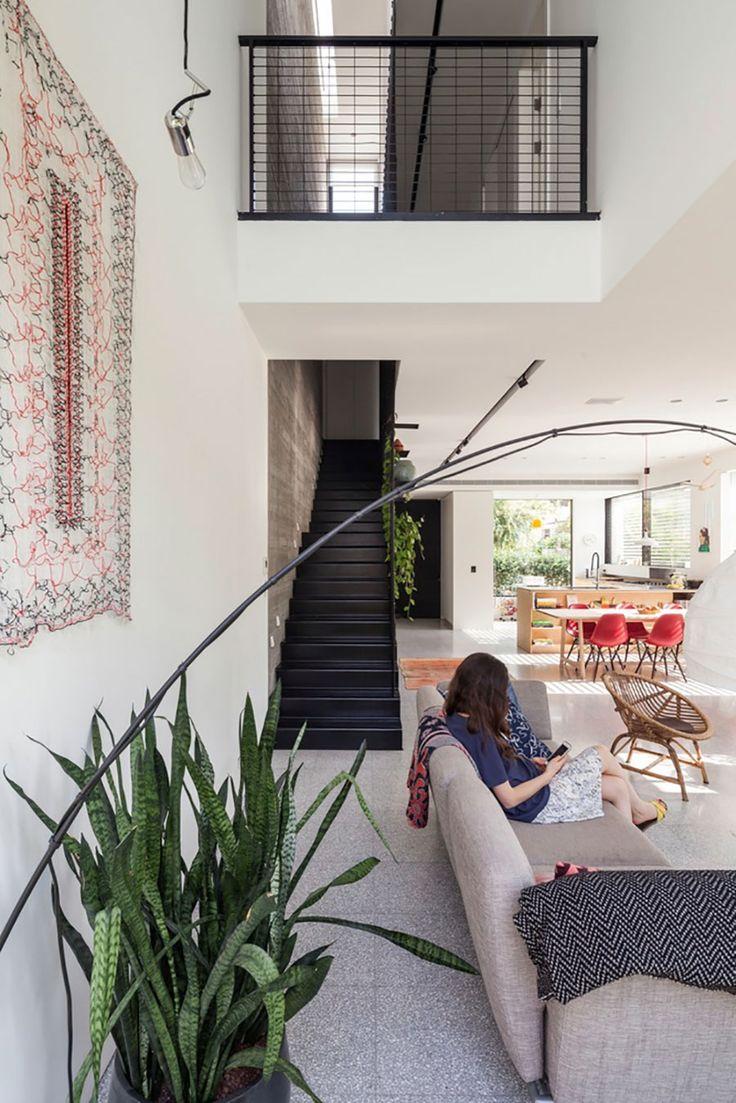 Decoração moderna com portas de vidro, poltrona cinza, escada preta, paredes brancas, plantas, mesa de madeira, cadeiras vermelhas e iluminação natural.